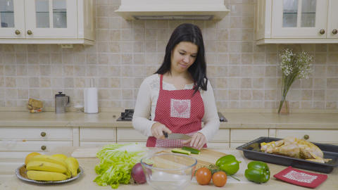 Housewife cuts cucumber for salad Footage