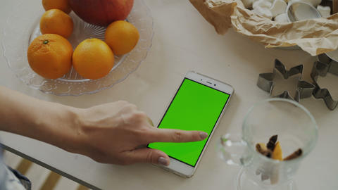 Closeup of woman's hand browsing smartphone with green screen on kitchen table Footage