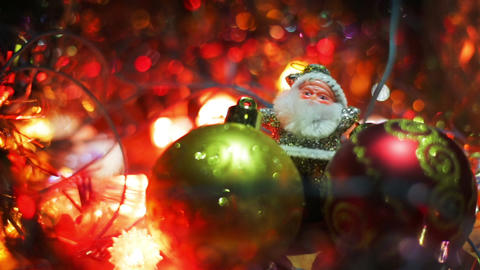 Miniature Santa Claus figure between two toy Hanging Baubles for a Christmas Footage
