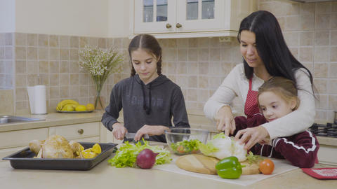Daughters help mother to cook the dinner Footage