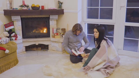 Married couple relaxing near fireplace and reads the book Footage
