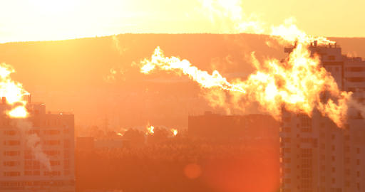 Smoke from pipes in high-rise residential building, early morning, backlight. Footage
