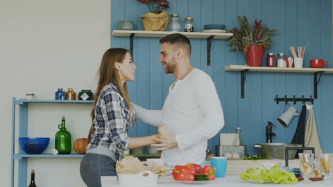 Slowmotion of joyful young couple have fun dancing while cooking in the kitchen Footage