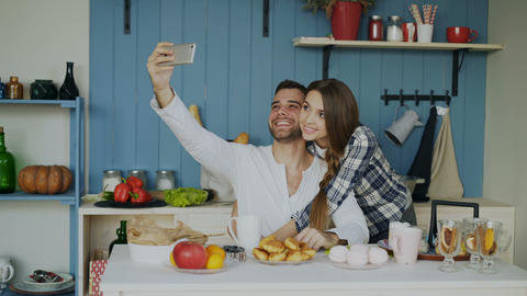 Young happy couple taking selfie portrait while having breakfast in the kitchen Footage