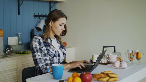 Young concentrated woman working in kitchen using laptop computer during Footage