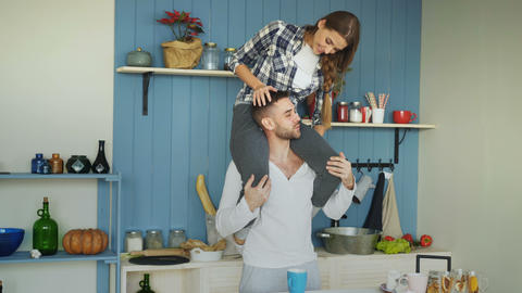 Happy young couple having fun in kitchen at home. Girl is sitting on boyfriend's Live Action