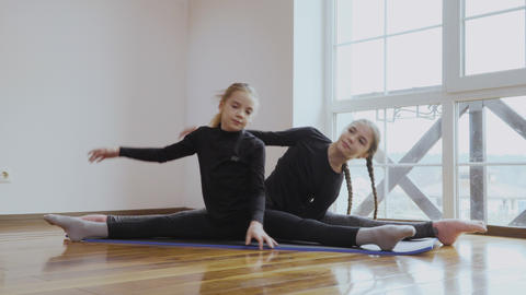 Two little sisters training their flexibility at home Footage