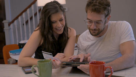 Handsome man and beautiful woman in early 30s shopping online together in their Footage