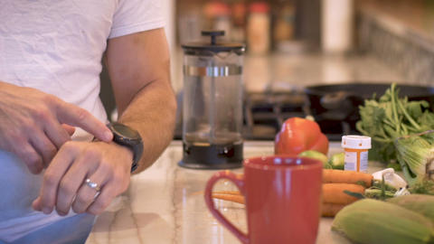 Fit man looking at and tapping his smart watch in the morning in his kitchen - Footage