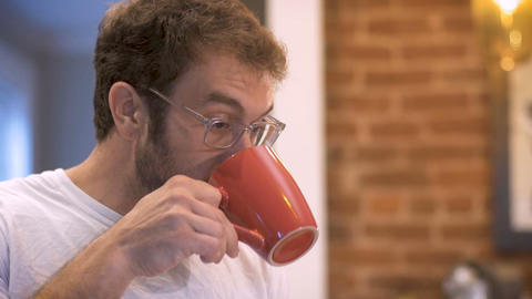 Attractive man taking a drink of coffee in the morning and swallowing - slow Live Action