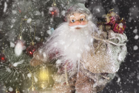 Santa Claus Outdoors Beside Christmas Tree in Snowfall Carrying Gifts to フォト
