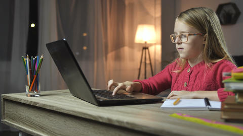 Cheerful child doing homework online with laptop Image