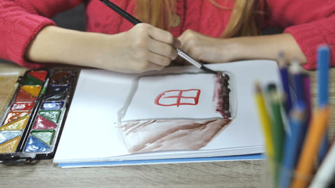 Child's hands drawing a house with paintbrush Footage