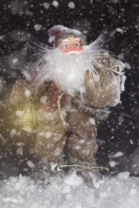 Santa Claus Outdoors Beside Christmas Tree in Snowfall Carrying Gifts to Photo