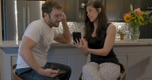 Gorgeous woman with an attractive man laughing and looking at a cell phone Footage
