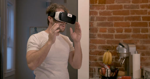 Handsome young millennial male starting his day putting on virtual reality head 画像