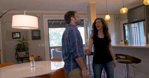 Attractive young excited woman leading a handsome man through their new house Image