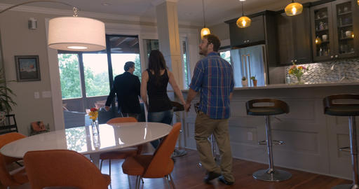 Attractive young couple in early 30s holding hands looking at a new modern home Footage