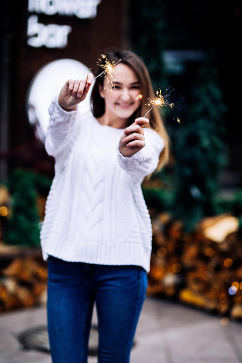 Happy white girl with long dark hair in sweater, garlands in bokeh, holiday cozy Photo