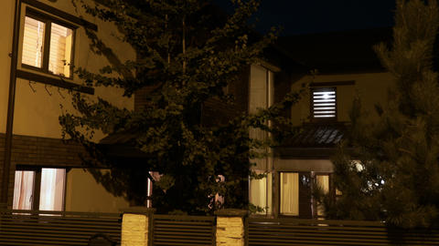 Establishing shot of smart residential house with lights turning on and off on Footage