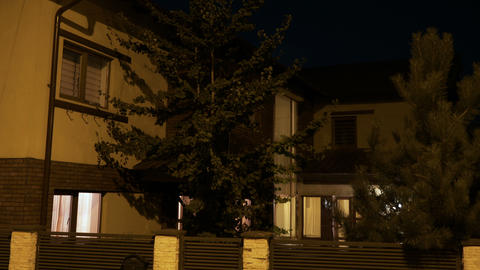 Smart house with pine trees from residential neighborhood turning on lights when Footage