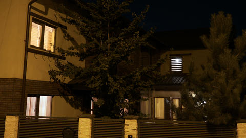 Establishing shot of a residential smart house turning lights on and off in each Footage