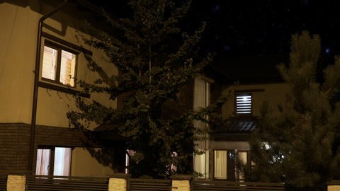 Exterior of a smart house illuminated gradually in every room in a residential Live Action