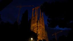 Sagrada Familia at night time, dim illuminated against dark blue sky Footage