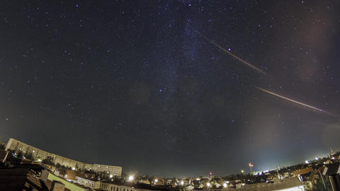 The milky way over a light poluted city, panoramic rooftop pan shot Footage