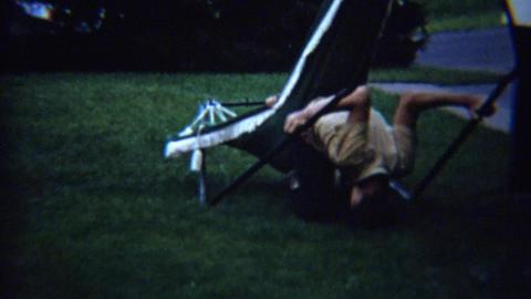 1963: Kid goofing on outdoor summer hammock flipping ride Footage
