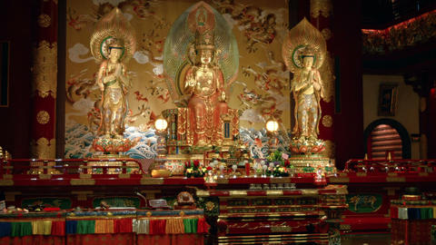 Buddha images stand over a colorful altar inside a temple in Singapore Live Action