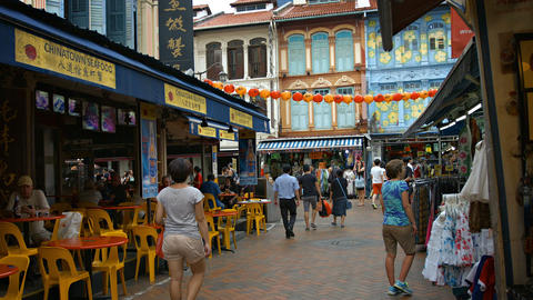 Tourists stroll through past shops and eateries in Singapore Chinatown district Live Action