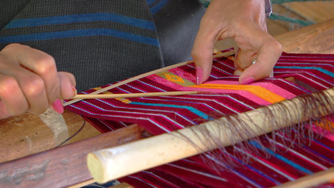 Balinese artist weaves colorful patterns using a traditional. wooden loom ビデオ