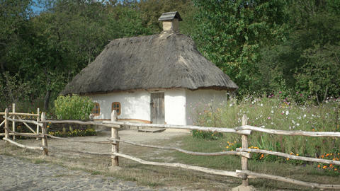 Old fashioned thatched roof cottage in rural. eastern European village Footage