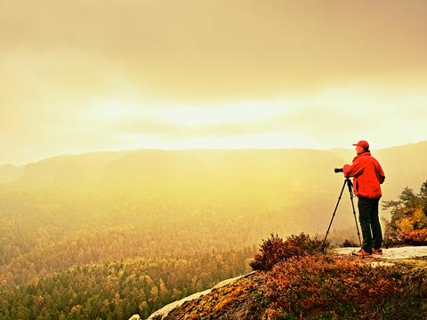 Art photographer on location takes photos with camera on peak of rock. Foggy Photo