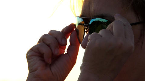 Woman takes off her sunglasses and looks at sunset in slo-mo Footage