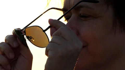 Woman takes off her sunglasses and smiles at sunset in slo-mo Footage