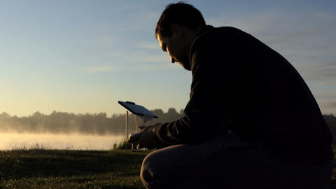 Young man sits and looks at a drone dashboard on a lake bank Archivo