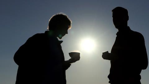 Two young men drink hot tea at a picturesque sunset in 4k Filmmaterial