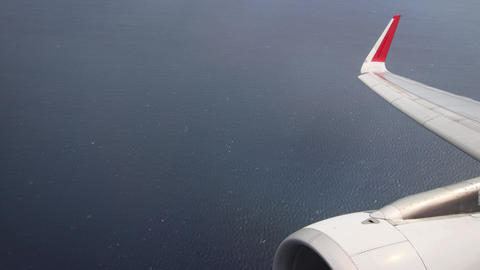 Aerial Passenger Perspective of Open Ocean with Airplane Wing and Engine Live Action