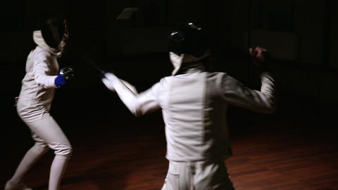 Young man and woman dressed in costumes for fencing train in the hall. Dark Live Action
