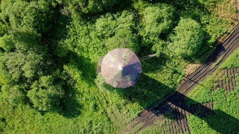 Rise above the water tower with rotation. HEAD OVER SHOT. View of the dirt road, Footage