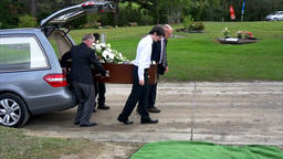 shot of casket being carry to burial site at cemetery Footage