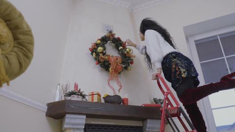 Beautiful girl prepares to christmas and decorates the wall over the fireplace Footage