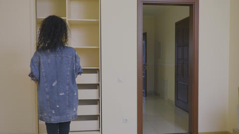 Pretty girl put a box with things in an empty wardrobe in a new house Footage