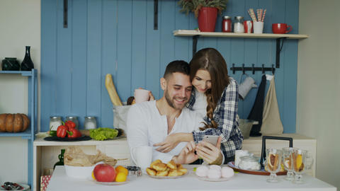 Attractive couple meet in the kitchen at breakfast time and using smartphone for Footage