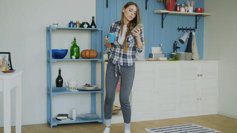 Cheerful happy girl dancing and singing in kitchen while surfing social media on Footage