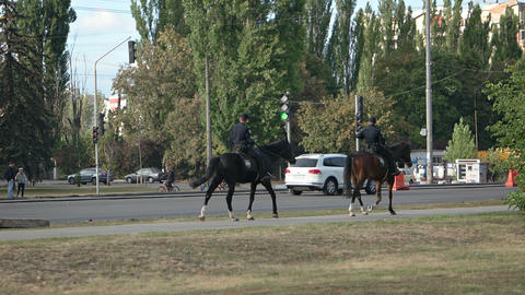 Horse Mounted Police Officers Patrol the Sidewalks along a Busy Street Footage