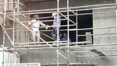 Construction Workers Taking a Break on a High Scaffold at their Work Site Live Action