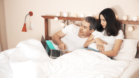 Husband and pregnant wife using laptop in their bed. Online shopping Footage